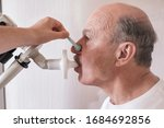 Small photo of Senior hispanic man man testing breathing function by spirometry. Diagnosis of respiratory function in pulmonary disease