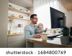Small photo of Young parent working from home while holding his baby boy on his lap while they both watch to the screen.