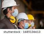 Workers wear protective face masks for safety in machine industrial factory. - stock photo