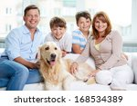 Stock photo cheerful family with their pet sitting on sofa at home 168534389
