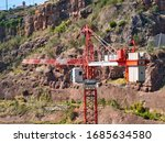 Small photo of Funchal, Portugal - Mar 16, 2020: The top of the mast, the slewing unit, working arm / jib, operator cab and machinery arm with counter weights on a tower crane operating near Monte, Funchal, Madeira.