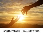 Silhouette of reaching, giving a helping hand, hope and support each other over sunset background.