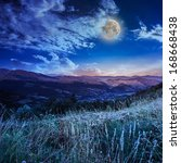 full moon in sky over the top of a high mountain - stock photo