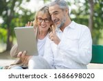 Technology connect and modern elderly lifestyles concept. Aged senior couple waving hands greeting grandkids via facetime video call internet conference outdoors in the park