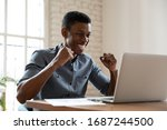 Small photo of Joyful African office worker sitting at workplace desk looking at pc screen clenched fists make Yes gesture receive great offer read fantastic news, student celebrating successful exam passing concept