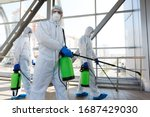 Professional workers in hazmat suits disinfecting indoor accommodation, pandemic health risk, coronavirus - stock photo