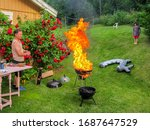 Small photo of Family, father and child having a outdoor garden barbecue grill party in the backyard. Fail with grill on fire, inferno with big flames.
