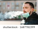 Small photo of Coronavirus. Smoking. Closeup man with mask during COVID-19 pandemic smoking a cigarette at the street. Smoking causes lung cancer and other diseases. The dangers and harm of smoking.