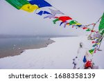 Small photo of Colorful prayer flags with mantra 'Om Mani Padme Hum' in Sanskrit meaning compassion, ethics, patience, diligence, renunciation and wisdom in English flying in winds at Chandratal lake.