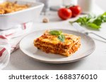 Small photo of Piece of tasty hot lasagna served with a basil leaf on a gray plate. Italian cuisine, menu, recipe. Homemade meat lasagna. Close up, side view