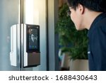 Small photo of Authentication by facial recognition concept. Biometric admittance control device for security system. Asian man using face scanner to unlock glass door in office building.