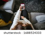 Small photo of Young woman sitting on sofa video calling her friends with smartphone that live far away from home - Millennials having fun together - Top view