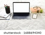 Small photo of flat lay, Work form home for CORONAVIRUS or COVID-19 prevention concept in the bedroom with blank screen laptop computer and mobile phone, document graft and stack of book, supplies