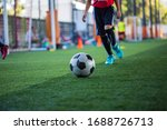 Small photo of Children playing control soccer ball tactics cone on grass field with for training background Training children in Soccer