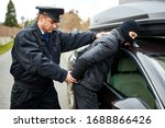 Small photo of Police officer arrests car thief in the act and handcuffs him on arrest