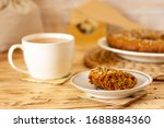 Cup of fragrant green tea  and aromatic appetizing carrot cake with sunflower seeds, raisins and sesame seeds in beautiful kitchen on natural  serving tray, spring fragrant dish, healthy and tasty pie