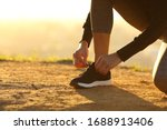 Small photo of Closeup of runner woman hands tying shoelaces of shoes on the ground at sunset