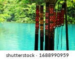 Chinese minority Miu hand embroidered colorful belts hanging on rope with water scenery in background