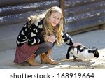 A pretty young girl petting a barn cat while it eats. - stock photo