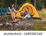 Couple Sitting At Camping Site...