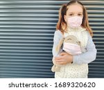 A girl a primary school student in a medical mask stands and hugs her favorite toy.  Sad girl in a medical mask hugs an infringer in a medical mask, pandemic concept. - stock photo