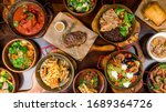 Small photo of Assorted food set on table, Pasta with seafood, steak ribeye, club sandwich, turkey with black rice, salad with kinoa, tartar from beef, fried loungustine