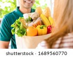 smiling delivery man giving... | Shutterstock . vector #1689560770