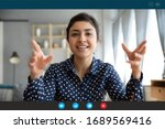Small photo of Headshot portrait screen view of smiling young Indian woman sit at home talk on video call with friend or relative, happy millennial biracial female speak online using Webcam conference on computer