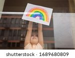 Kid painting rainbow during Covid-19 quarantine at home. Girl near window. Stay at home Social media campaign for coronavirus prevention, let