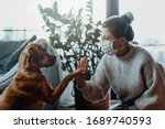 Small photo of Woman wearing a protective face mask cuddles, plays with her dog at home because of the corona virus pandemic covid-19