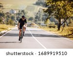 Small photo of Front view of bearded man with athletic body shape in protective helmet and glasses riding bicycle with beautiful nature around. Concept of self discipline and motivation.