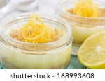 Lemon Cheesecake - Individual lemon cheesecakes with biscuit base and whipped cream topped with lemon rind in glass bowls. - stock photo