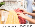 Small photo of Female hand choosing clothes for checked pattern cotton dress on the rack in cloth shop at cloth shop department store. Check price, discount and promotion of clothing product.