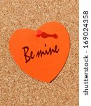 Red paper heart with Be mine text pinned to the corkboard - stock photo