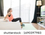 Small photo of Video streaming Stay home.home fitness workout class live streaming online.Asian woman doing strength training cardio aerobic dance exercises watching videos in the living room at home.Covid-19.