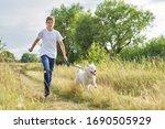 Teen Boy Running With Dog ...