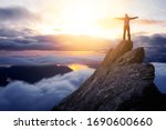 Small photo of Adventurous Man Hiker With Hands Up on top of a Steep Rocky Cliff. Sunset or Sunrise. Landscape Taken from British Columbia, Canada. Concept: Adventure, Explore, Hike, Lifestyle. Composite.