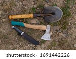 ax shovel knife camping tools on ground closeup - stock photo