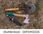 ax shovel knife camping tools on ground closeup - stock photo