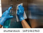 Small photo of Closeup of old staff hand using wet wipe cleaning an elevator push button control panel with a blue sanitizer bottle.Disinfection,cleanliness and healthcare,Anti Corona virus,COVID-19.Selective focus.