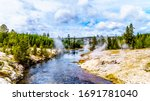 Hot water from the Fan Geyser and several other geysers and hot springs flowing into the Firehole River in the Upper Geyser Basin along the Continental Divide Trail in Yellowstone, Wyoming, USA