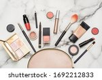 Small photo of Beautician on a marble background with a makeup brush, tonal foundation, lipstick, lip liner, blush and eye shadow. The concept of expensive luxury cosmetics