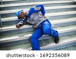 Worker Man Lying On Staircase...