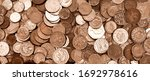 Small photo of UK currency, hundreds of British copper and silver colored coins randomly piled ontop of each other, one pound coins, fifty pence, twenty pence, two pence, one pence