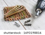 Metal big Screws organized in stack with screwdriver drill and screwdriver heads (bits) on wooden background. Close up stock photo. - stock photo