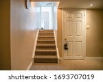 Small photo of Stairs going out of the basement. Basement door, walkout stairs and at walkout door there are shoes lying around