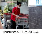Small photo of Lima, Peru - April 4 2020: Supermarket worker disinfecting shopping carts and wearing a mask amid coronavirus outbreak in South America. Cleaning shopping carts outside a Wong store in COVID-19 times.