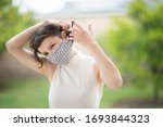 Small photo of A pretty caucasian woman put on a fabric handmade mask on her face. Due to Covid-19 pandemic, it is recommended that everyone wear face covers while in public.