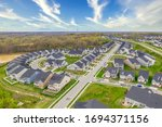 Aerial view of the geometrical curving American residential neighborhood, single family houses built close to each other with a cross street in Two Rivers Crofton Maryland with bue sky