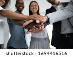 Small photo of Close up happy diverse business people putting hands together, showing support and unity. Multiracial colleagues involved in team building activity. Staff training concept, start working together.